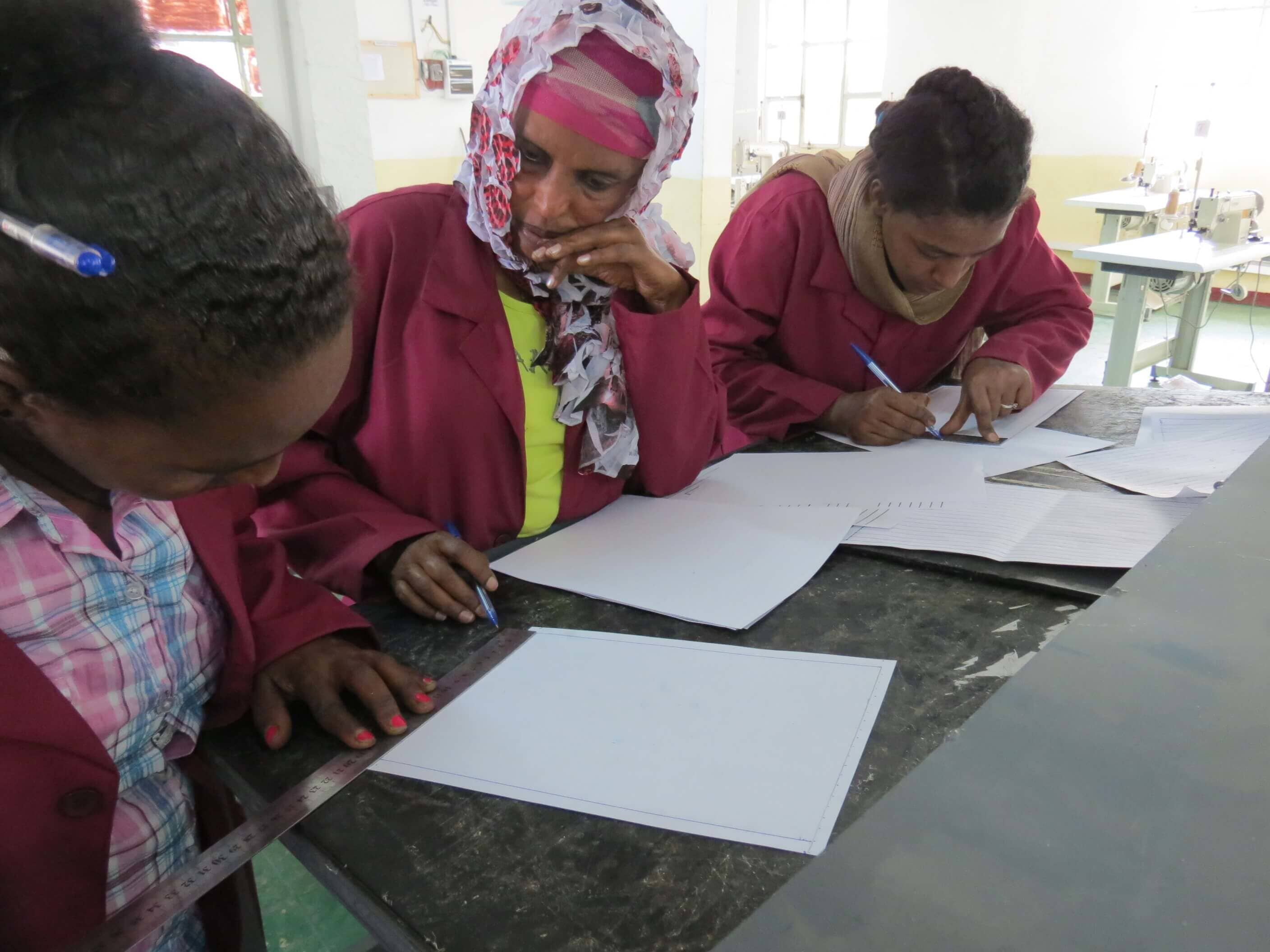 Trainees measuring and drawing