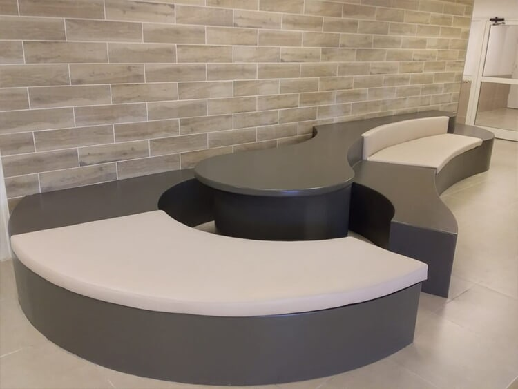 Construction of a styled bench for a public building. The bench is coated with fiberglass and painted using extremely durable paint